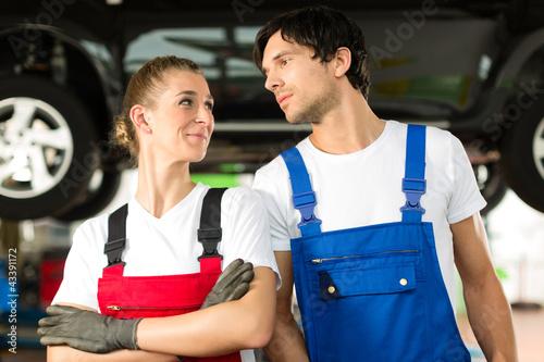Auto Mechaniker Paar steht in Autowerkstatt