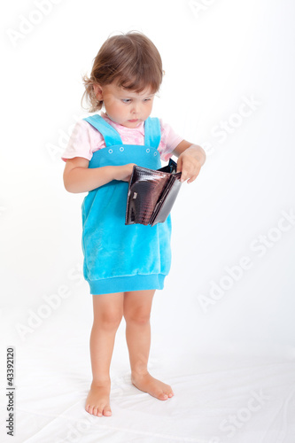 Little girl looking in a purse. Girl with purse