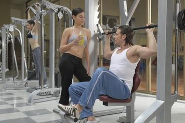 Hombre joven haciendo gimnasia, levantando pesas
