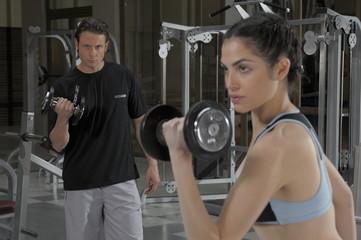 pareja levantando pesas en gimnasio
