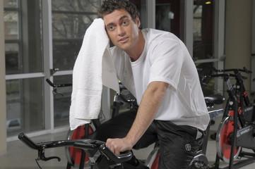 Hombre joven haciendo gimnasia en bicicleta
