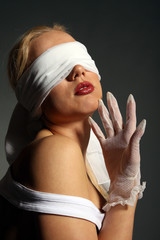 young girl blindfolded and wearing white gloves