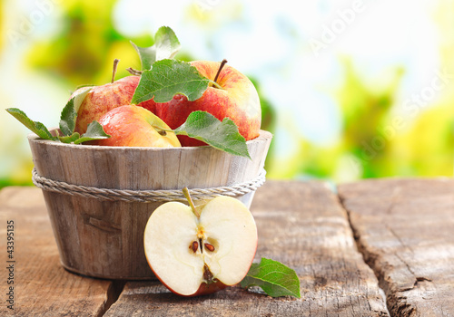 Wooden tub full and a halved fresh apple