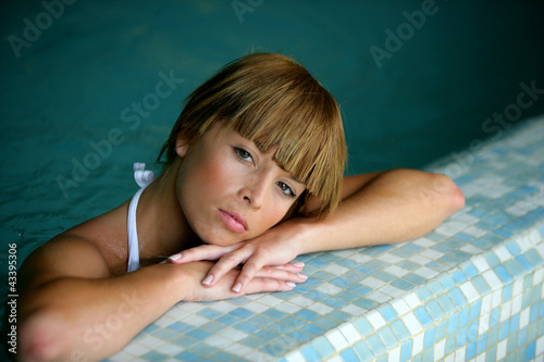 Woman leaning against the edge of a swimming pool
