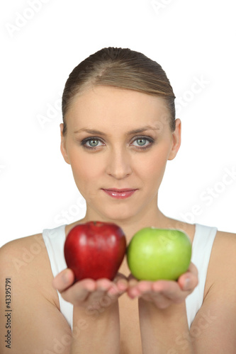 Blond holding green and red apples