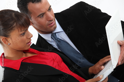 Two business people stood working on laptop