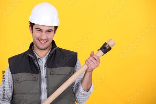 Builder with a wooden handled tool