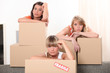Three woman leaning on brown cardboard boxes