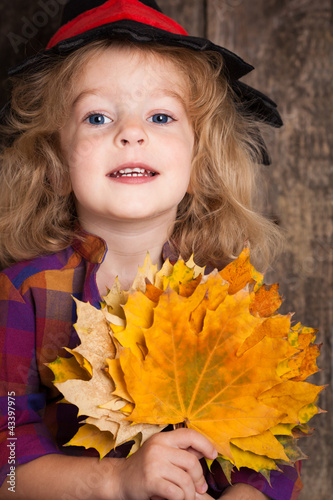 Kid with autumn leaves