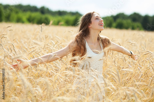 Woman in the wheat field with arms outstretched