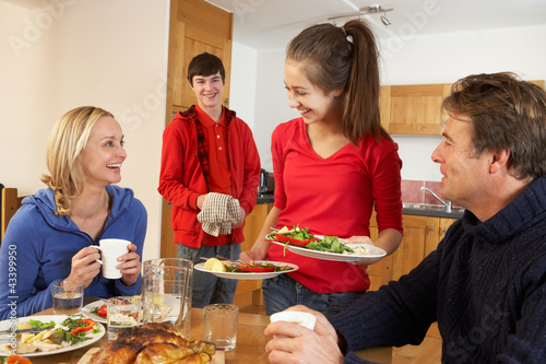 Helpful Teenage Children Serving Food To Parents In Kitchen