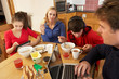 Teenage Family Using Gadgets Whilst Eating Breakfast Together In