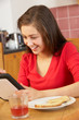 Teenage Girl Using Tablet Computer Whilst Eating Breakfast