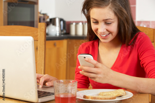 Teenage Girl Using Laptop And Mobile Phone Whilst Eating Breakfa