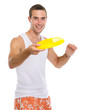 Happy young man playing with flying disc