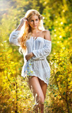 Portrait of a sensual young blonde female on field in sexy short