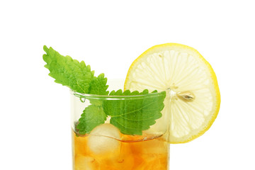 Ice  tea in glass  with lemon and melissa isolated on  white