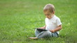 Child working with the Tablet PC sitting on grass