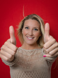 Young woman smiling with thumbs up color image
