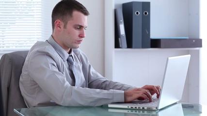 Depressed businessman working on a laptop