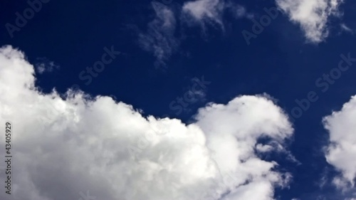 Time lapse clouds over blue sky