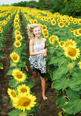 Happy young blonde girl running in the field of sunflowers