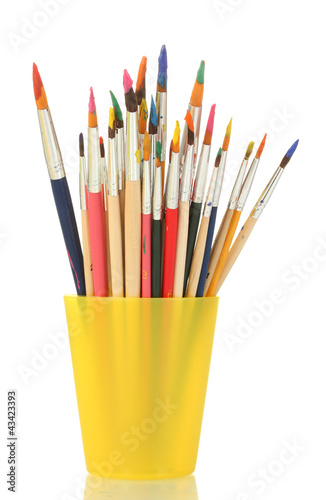 Paint brushes with gouache in cup isolated on white