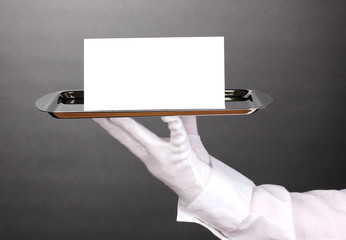 Hand in glove holding silver tray with blank card