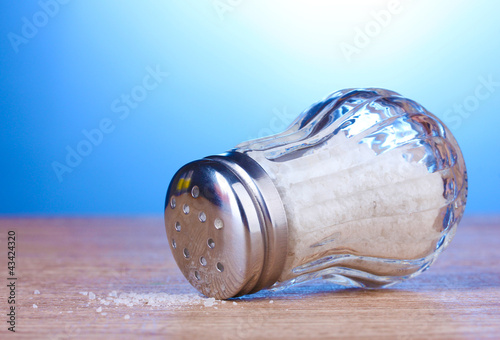 Glass saltcellar with salt on wooden table on blue background