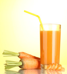 glass of carrot juice on yellow background