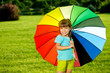 Smiling Little girl Kid in park with colorfull umbrella
