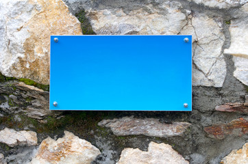 a blank blue metal signboard on a brick wall