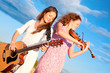 Two young women playing guitar and violin outdoors