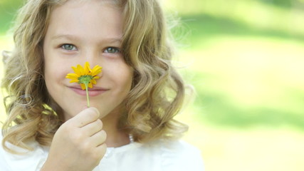 Little girl smelling a daisy flower in the meadow