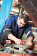 auto mechanic at car engine repair work