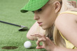 girl's playing with golf ball, she is in profile