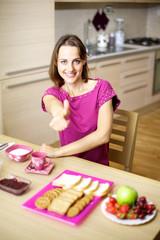 Woman in pajamas having breakfast thumb up