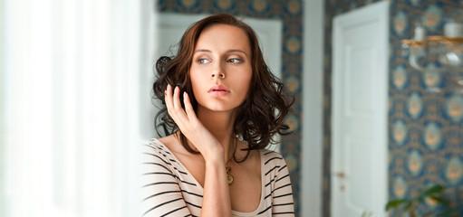 Beautiful woman standing near window. Beauty fashion portrait