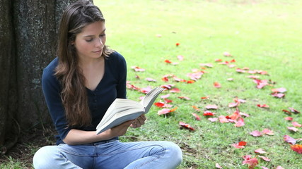 Woman reading a book in a park