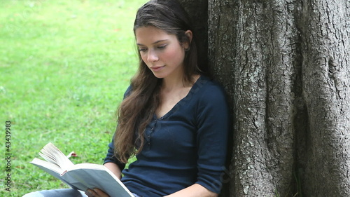 Woman sitting against a tree while reading a book