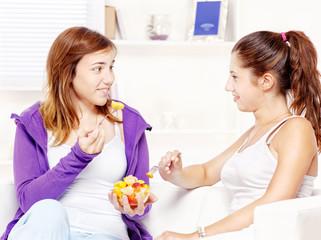 Teenage girls chating and eating fruit salad