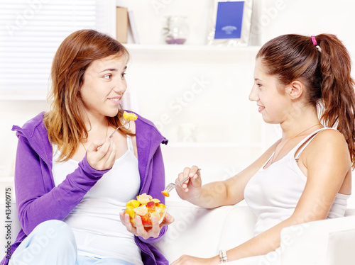 Teenage girls chating and eating fruit salad