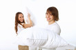 Young couple fighting with pillows
