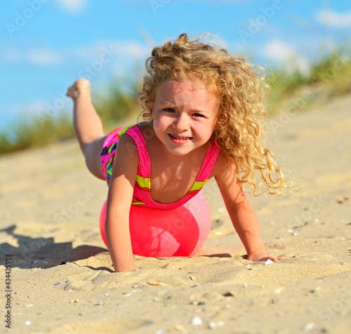 Портрет милой кудрявой девочки на пляже с мячом Эдуард Кислинский / Фотобанк Лори