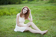 Redhead girl at green grass at village outdoor.