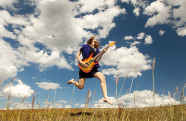 Redhead girl jumping with guitar at outdoor.