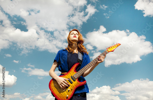 Redhead girl with guitar at sky background.