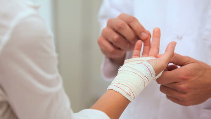 Doctor manipulating fingers of a patient