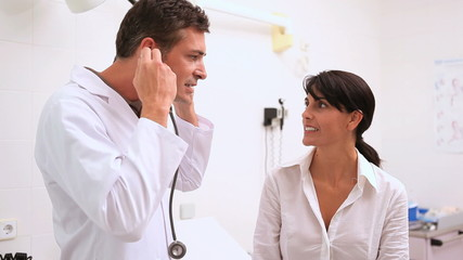 Doctor holding a stethoscope with a patient