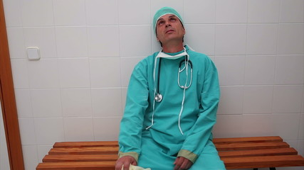 Exhausted surgeon sitting on a bench